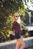Lycklig flicka för sport som poserar i sommar med skateboarden Stilfull lycklig hipsterkvinna med färgrik longboard i solnedgång  Royaltyfri Foto