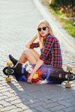 Lycklig flicka för sport som poserar i sommar med skateboarden Stilfull lycklig hipsterkvinna med färgrik longboard i solnedgång  Royaltyfri Bild