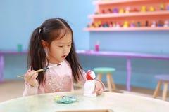 Lycklig flicka f?r litet barn som har gyckel som ska m?las p? stuckaturdockan inomhus arkivfoton
