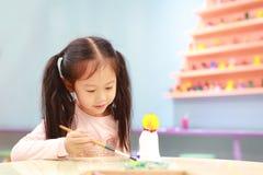 Lycklig flicka f?r litet barn som har gyckel som ska m?las p? stuckaturdockan inomhus arkivbild
