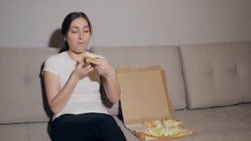 Lycklig flicka, i att äta pizza hemma lager videofilmer