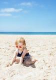 Lycklig flicka i den randiga baddräkten som spelar med sand på den vita stranden Royaltyfri Fotografi