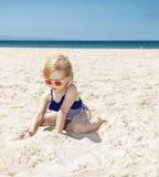 Lycklig flicka i den randiga baddräkten som spelar med sand på den vita stranden Fotografering för Bildbyråer
