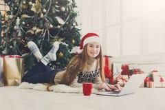 Lycklig flicka i den santa hatten som direktanslutet pratar på bärbara datorn Royaltyfria Bilder