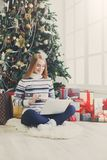 Lycklig flicka i den santa hatten som direktanslutet pratar på bärbara datorn Arkivbild