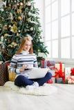 Lycklig flicka i den santa hatten som direktanslutet pratar på bärbara datorn Arkivfoton