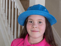 Lycklig flicka i en blå hatt inomhus Royaltyfri Bild