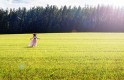 Lycklig flicka i en lång kjolkörning på fältet Arkivbilder
