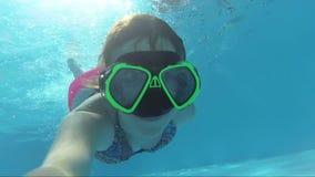 Lycklig flicka i en maskering under vattnet i simbassängblickarna in i kameran, bubblor, solstrålar lager videofilmer