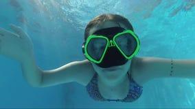 Lycklig flicka i en maskering under vattnet i simbassängblickarna in i kameran, bubblor, solstrålar stock video