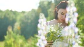 Lycklig flicka i ett fält med blommor i natur flicka i ett fält som ler kvinnan som rymmer en utomhus- bukett av blommor royaltyfri foto