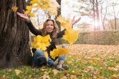 Lycklig flicka i färgrika sidor för höstskog Arkivbild