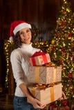 Lycklig flicka i hatt för jultomten` s med många julgåvor Arkivbilder