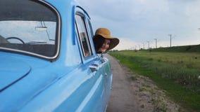 Lycklig flicka i hattbenägenhet ut ur retro fönster och att le för bil Ung lycklig kvinna som ut ser fönstret av den gamla automa stock video
