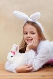 Lycklig flicka i kanindräkten som rymmer hennes vita kanin Arkivfoto