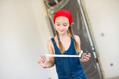 Lycklig flicka i röd hatt med reparationsutrustningrouletten Arkivbild