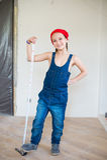 Lycklig flicka i röd hatt med reparationsutrustningrouletten Royaltyfri Fotografi
