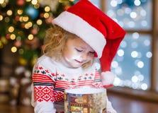 Lycklig flicka i röda Santa Hat som ser in i en gåvaask Arkivfoto