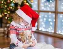 Lycklig flicka i röda Santa Hat som ser in i en gåvaask Royaltyfri Foto