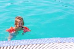 Lycklig flicka i simbass?ngen arkivfoto