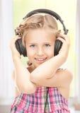 Lycklig flicka i stor hörlurar royaltyfri fotografi