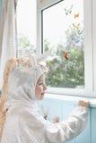 Lycklig flicka i Unicorn Costume Looks At Artificial fjärilar Arkivbild