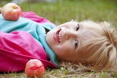 Lycklig flicka med äpplen Royaltyfria Bilder
