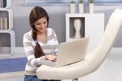 Lycklig flicka med bärbara datorn i vardagsrum Royaltyfri Foto