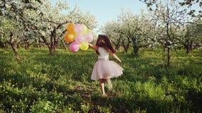 Lycklig flicka med ballonger som kör i den blommande trädgården stock video