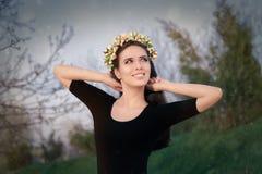 Lycklig flicka med den blom- kransen i natur Arkivbilder