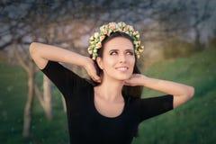 Lycklig flicka med den blom- kransen i natur Royaltyfria Bilder