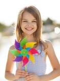 Lycklig flicka med den färgrika liten solleksaken Arkivfoto