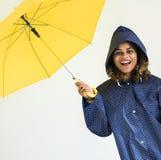 Lycklig flicka med det gula paraplyet royaltyfria bilder