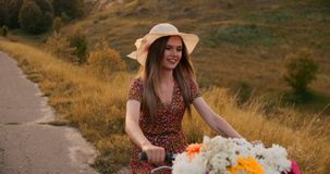 Lycklig flicka med en bukett av blommor som rider en cykel i en hatt och en sommarkortslutningsklänning lager videofilmer