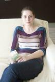 Lycklig flicka med euro på soffan Fotografering för Bildbyråer