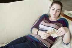 Lycklig flicka med euro på soffan Royaltyfria Foton