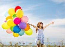 Lycklig flicka med färgrika ballonger Arkivbild