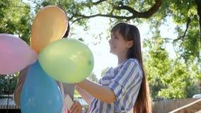 Lycklig flicka med färgrika ballonger som kör för att gratulera flickvännen på hennes födelsedag i parkera stock video