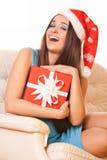 Lycklig flicka med gåvan i julhatt Arkivfoton