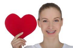 Lycklig flicka med hänglsen på tänder och röd hjärta arkivbild