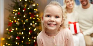 Lycklig flicka med hennes familj över julträd royaltyfri bild