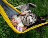 Lycklig flicka med hennes hund som vilar i hängmatta Arkivfoton