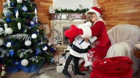 Lycklig flicka med jul gåva, unge som kramar Santa Claus, gåvor för bra och lydiga barn lager videofilmer