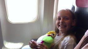 Lycklig flicka med kuddesammanträde på stol, i flygplan och att skratta för kabin medan fluga arkivfilmer
