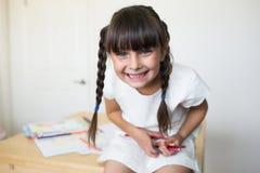 Lycklig flicka med kulöra blyertspennor i hand arkivbild
