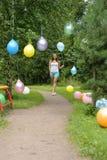 Lycklig flicka med kulöra luftballonger i en parkera Beröm cas Arkivfoton