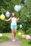 Lycklig flicka med kulöra luftballonger i en parkera Beröm cas Royaltyfria Foton
