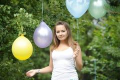 Lycklig flicka med kulöra luftballonger i en parkera Beröm cas Arkivfoto