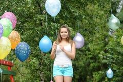 Lycklig flicka med kulöra luftballonger i en parkera Beröm cas Royaltyfria Bilder