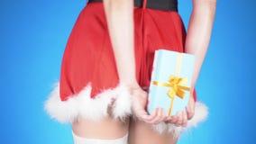 lycklig flicka med loppfallet ung attraktiv kvinna i en jungfru- dräkt för snö med en gåva som dansar på en blå bakgrund Närbild lager videofilmer